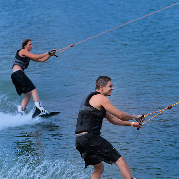 Young couple wakeboarding together, having fun